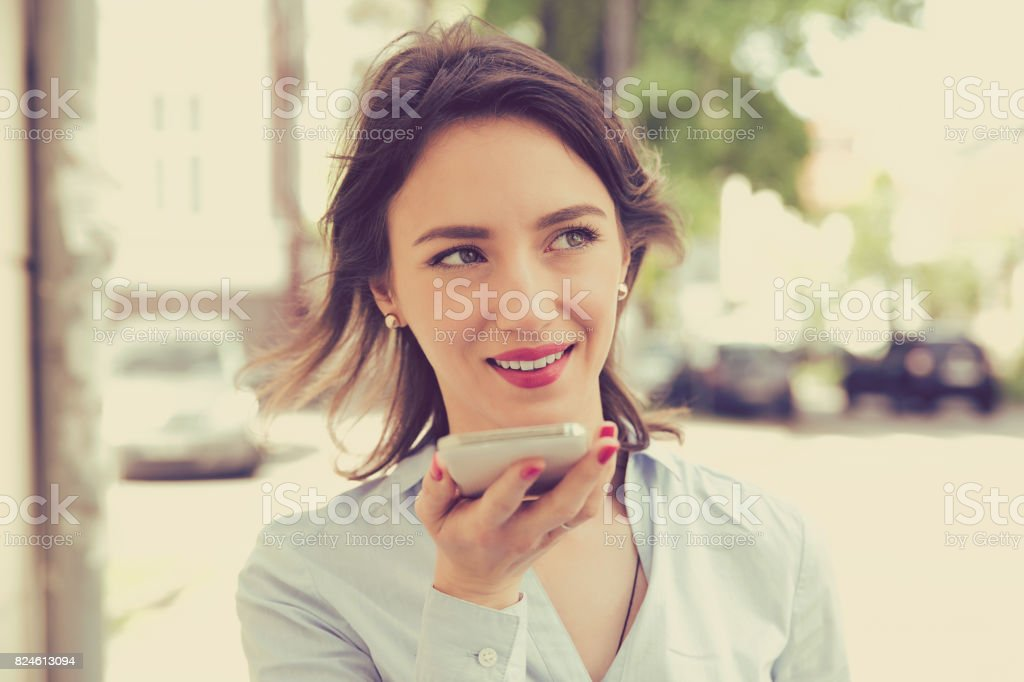 Woman using a smart phone voice recognition function online walking on a city street - Royalty-free Achievement Stock Photo