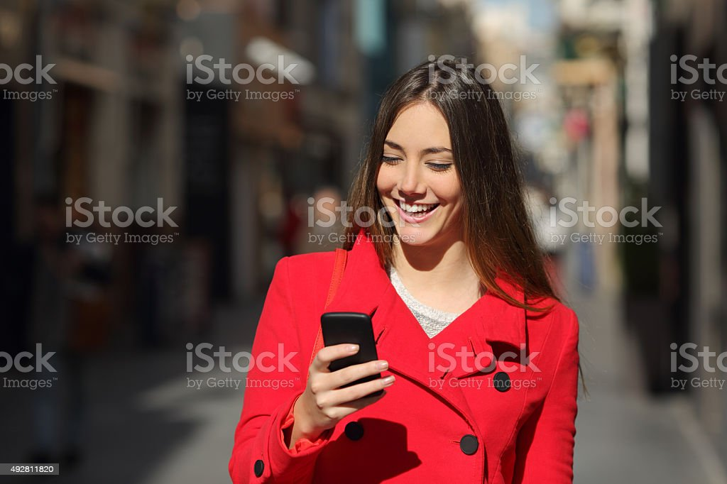 Woman using a smart phone while walk in the street stock photo