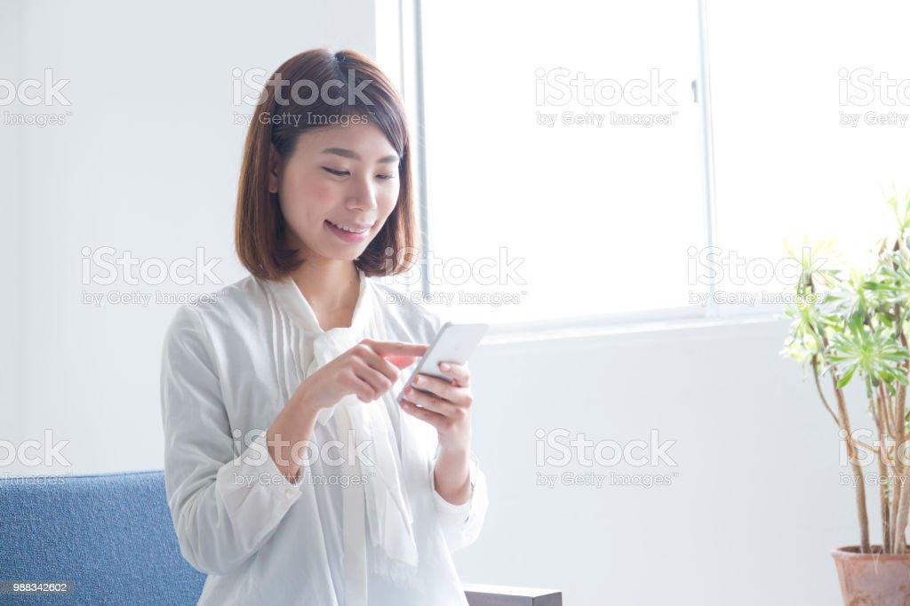 女性の部屋でスマートな携帯電話を使う ストックフォト