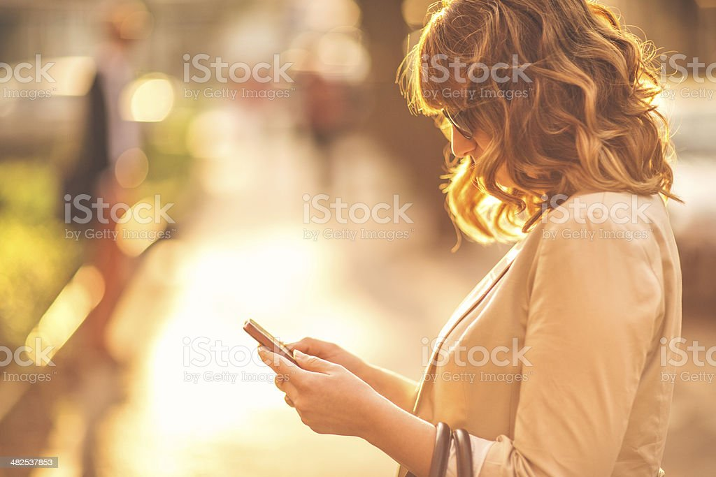 Woman using a smartphone outdoors stock photo