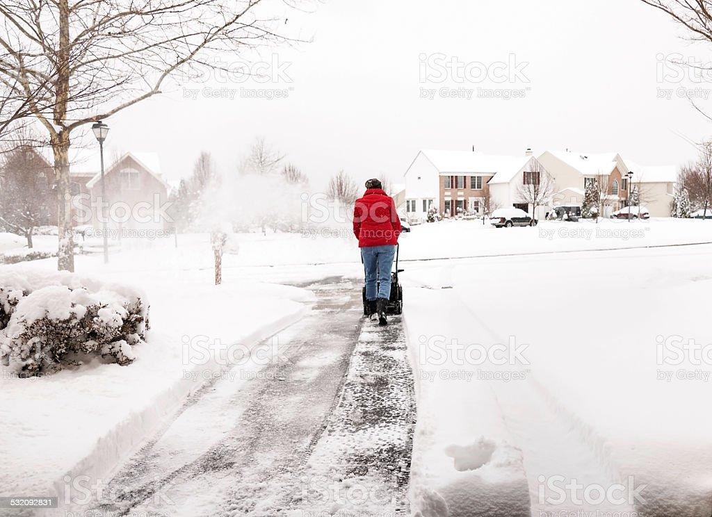 Woman using a snowblower stock photo
