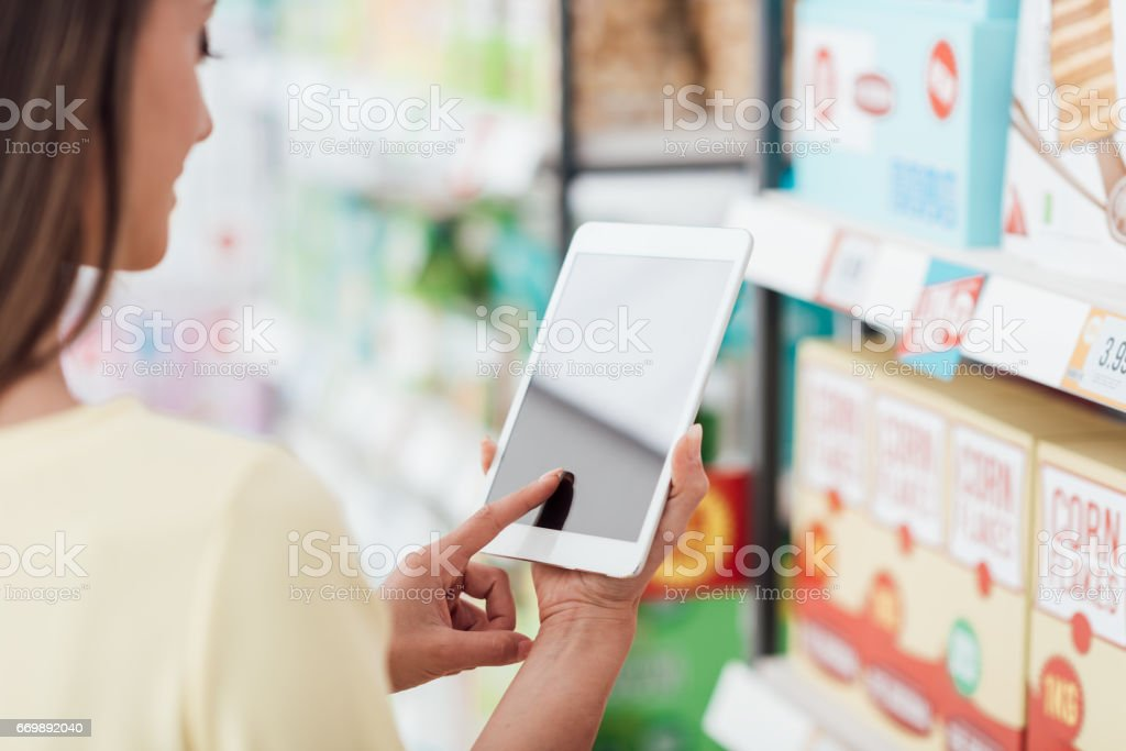 Woman using a tablet at the supermarket stock photo