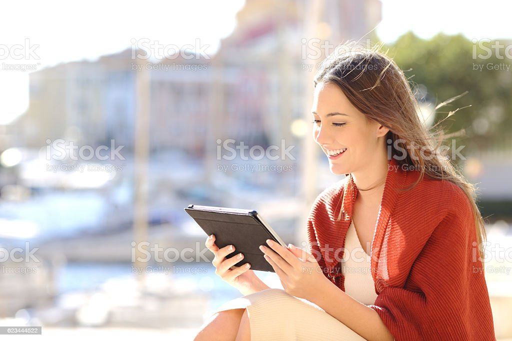 Woman using a tablet watching media content stock photo