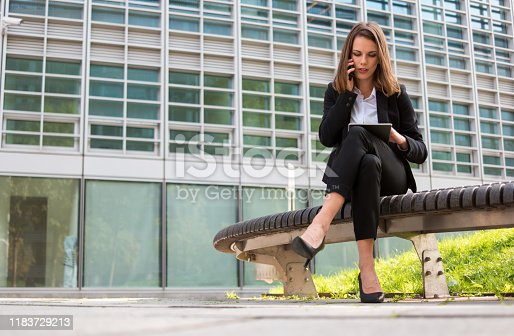 Portrait of a young woman using a tablet while talking on her mobile cell phone in front of her office