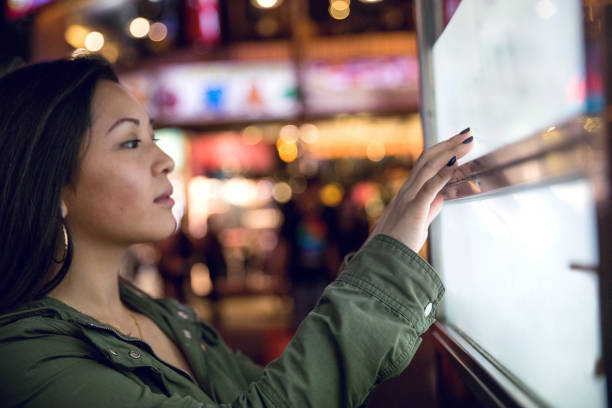 woman using a touch screen finding informations online in london city streets - interactivity stock photos and pictures