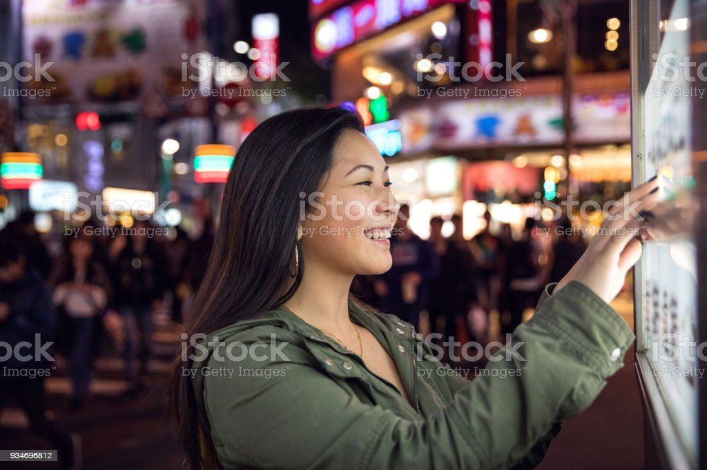 Woman using a touch screen finding informations online in London city streets stock photo
