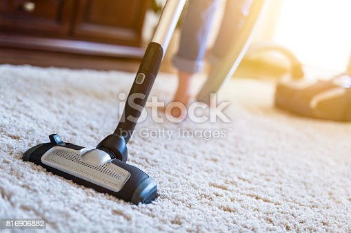 istock Woman using a vacuum cleaner while cleaning carpet in the house. 816906882