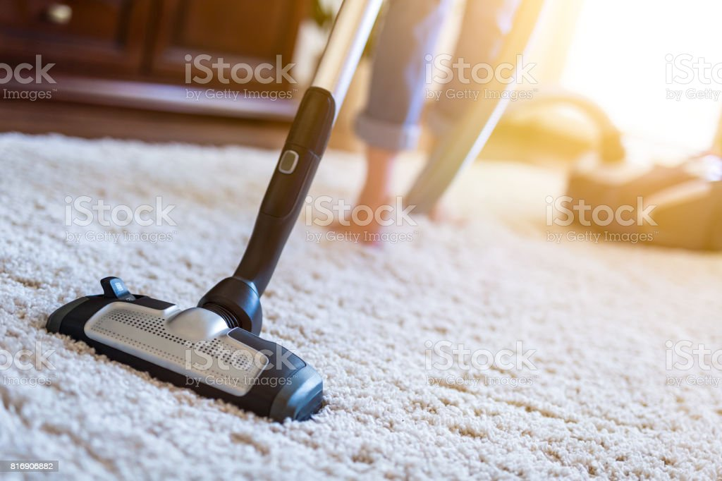 Woman using a vacuum cleaner while cleaning carpet in the house. stock photo