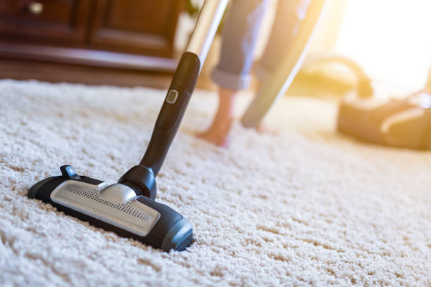 Woman using a vacuum cleaner while cleaning carpet in the house. Young woman using a vacuum cleaner while cleaning carpet in the house. cleaning equipment stock pictures, royalty-free photos & images