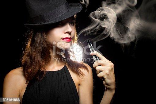 istock Woman Using a Vape for Smoking Alternative 528164863