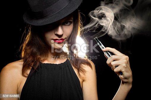 istock Woman Using a Vape for Smoking Alternative 528164885