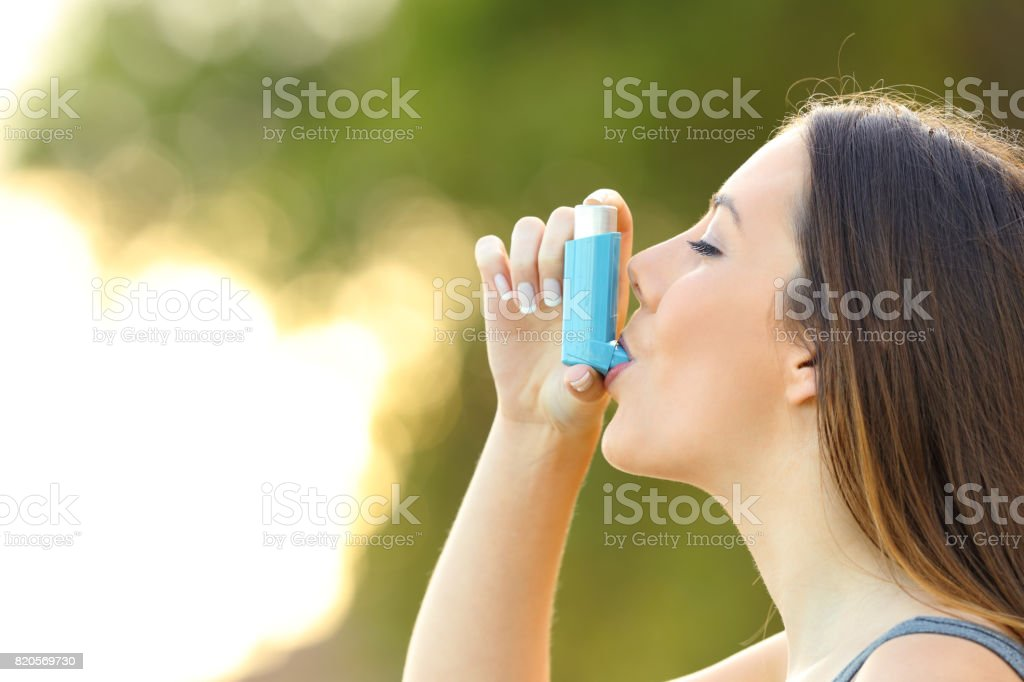 Woman using an asthma inhaler outdoors stock photo
