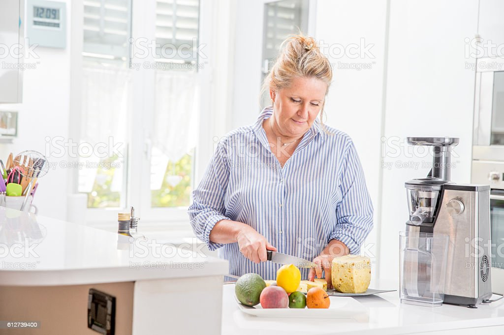 Woman using an Electric Juicer in her Kitchen stock photo