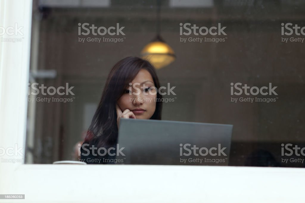 Woman Using an Ultrabook in a Coffee Shop stock photo