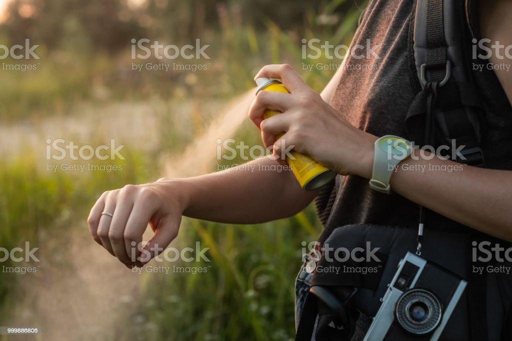 Woman using anti mosquito spray outdoors at hiking trip. stock photo