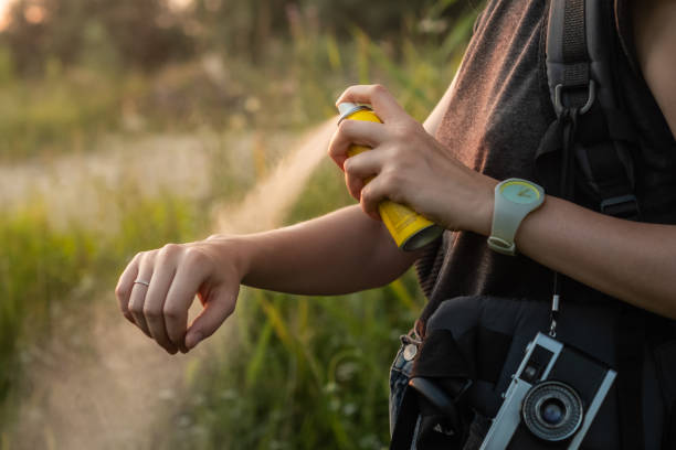 woman using anti mosquito spray outdoors at hiking trip. - mosquito stock photos and pictures