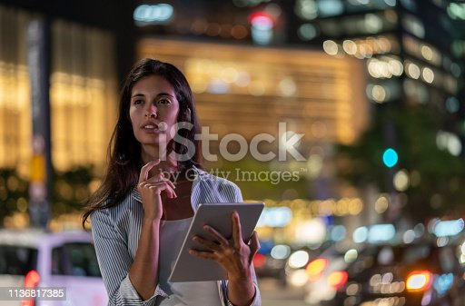 istock Woman using app on a tablet computer on the street at nighttime 1136817385