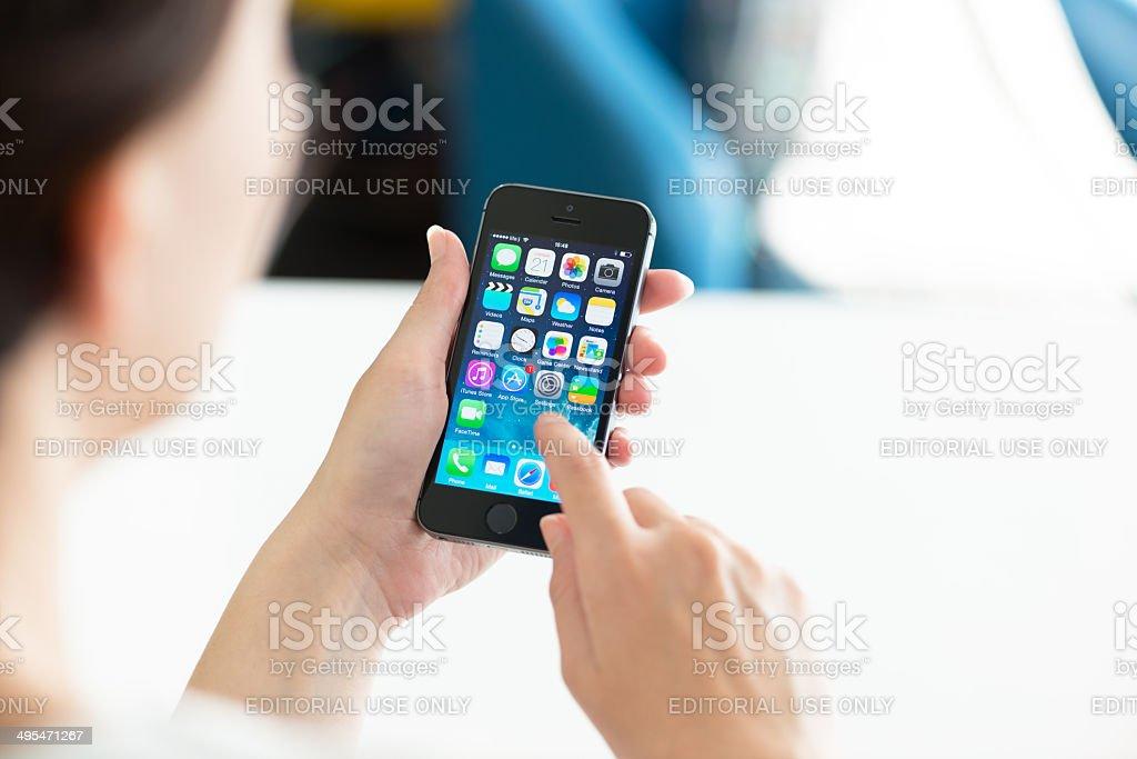 Woman using Apple iPhone 5S stock photo