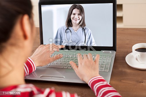 istock woman using application call with clinic 1147862099