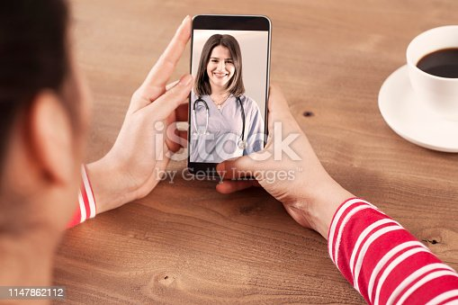 istock woman using application call with clinic 1147862112