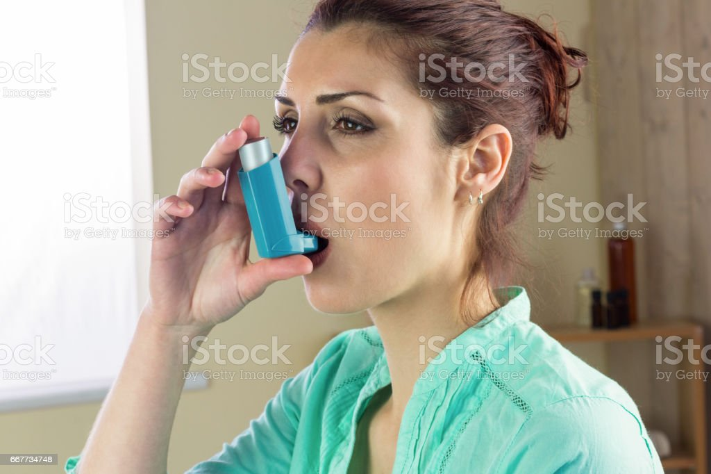Woman using asthma inhaler at home stock photo