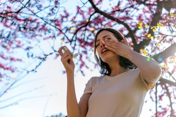 frau mit asthma-inhalator im freien - heuschnupfen stock-fotos und bilder