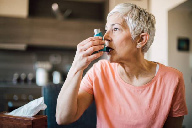 Woman using asthma inhaler stock photo