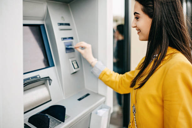 Woman using ATM machine Woman using ATM machine banks and atms stock pictures, royalty-free photos & images