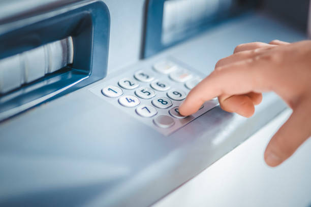 frau mit geldautomaten geld abheben - bankkonto stock-fotos und bilder
