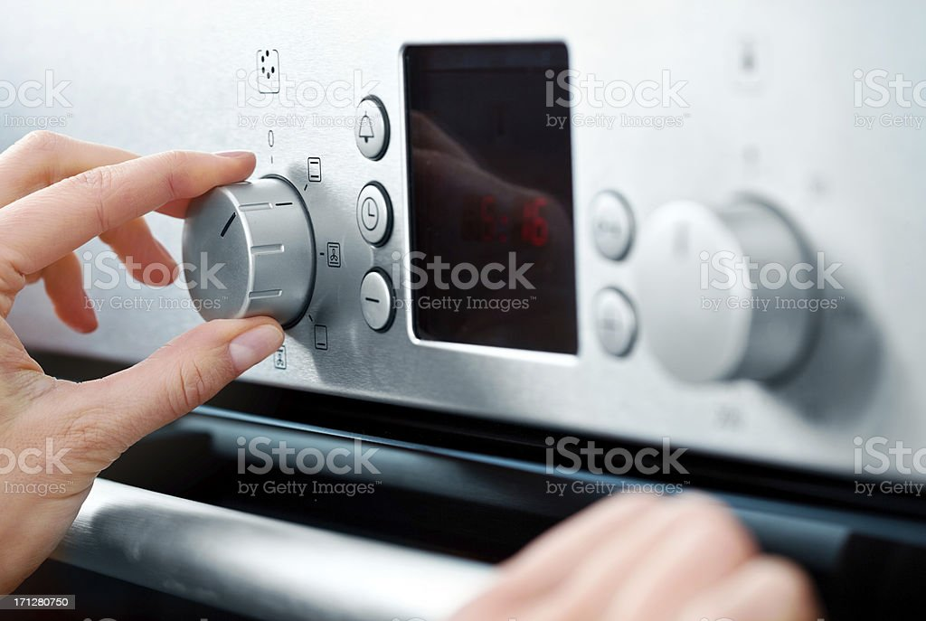 Woman using baking-oven stock photo