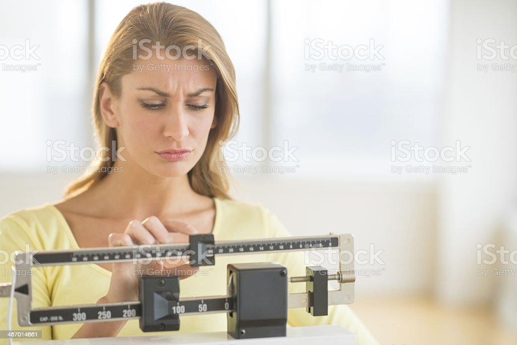 Woman Using Balance Weight Scale At Gym stock photo