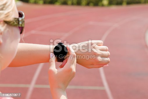 831622420 istock photo Woman using black smart watch at stadium track. Checking heart rate before and after workout. Monitoring of daily health with device. Close up. Place for text, logo or mobile app on empty screen. 1180820617