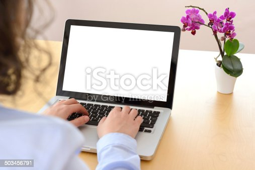 Woman using blank screen laptop at home.