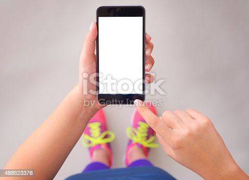Woman wearing sports clothing and using blank white screen smart phone.