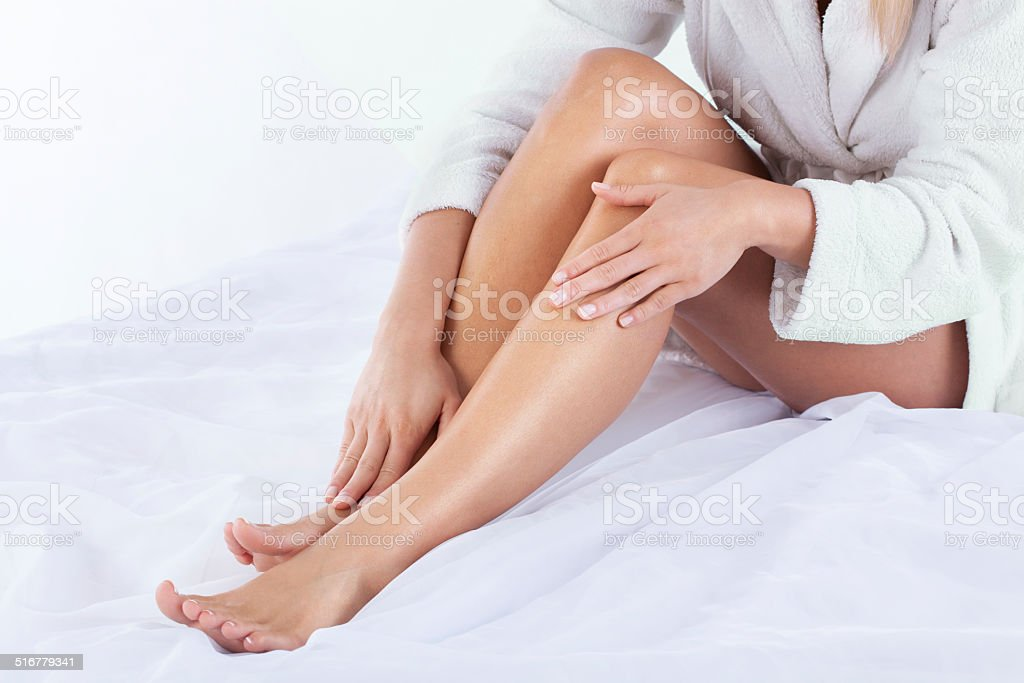 Woman using body lotion stock photo