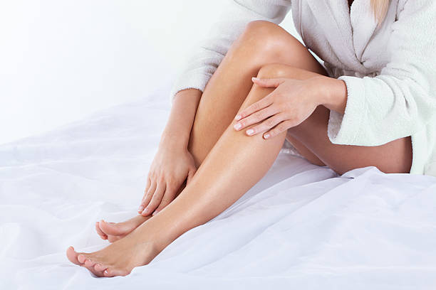 woman using body lotion - human leg stock photos and pictures