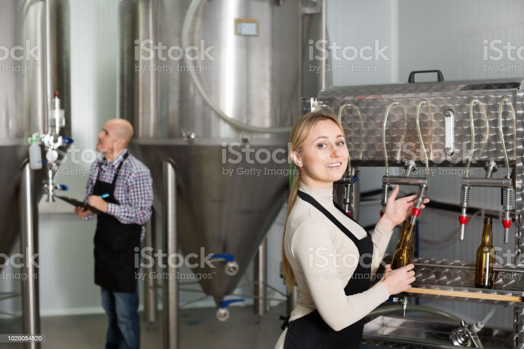 Woman using bottling equipment on brewery stock photo