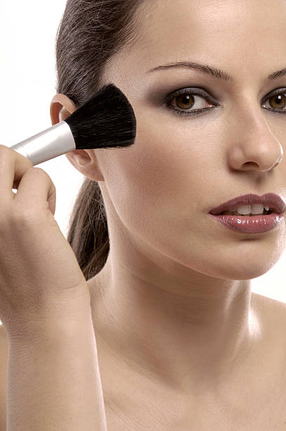 woman using brush for make-up stock photo