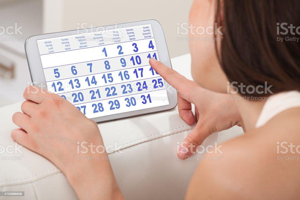 Mujer usando el calendario en tableta Digital en su hogar - foto de stock