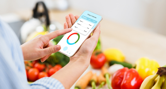 Woman using calorie counter application on her smartphone while cooking healthy lunch in kitchen. Fresh tasty vegetables and fruits lying on table on background, creative collage, panorama