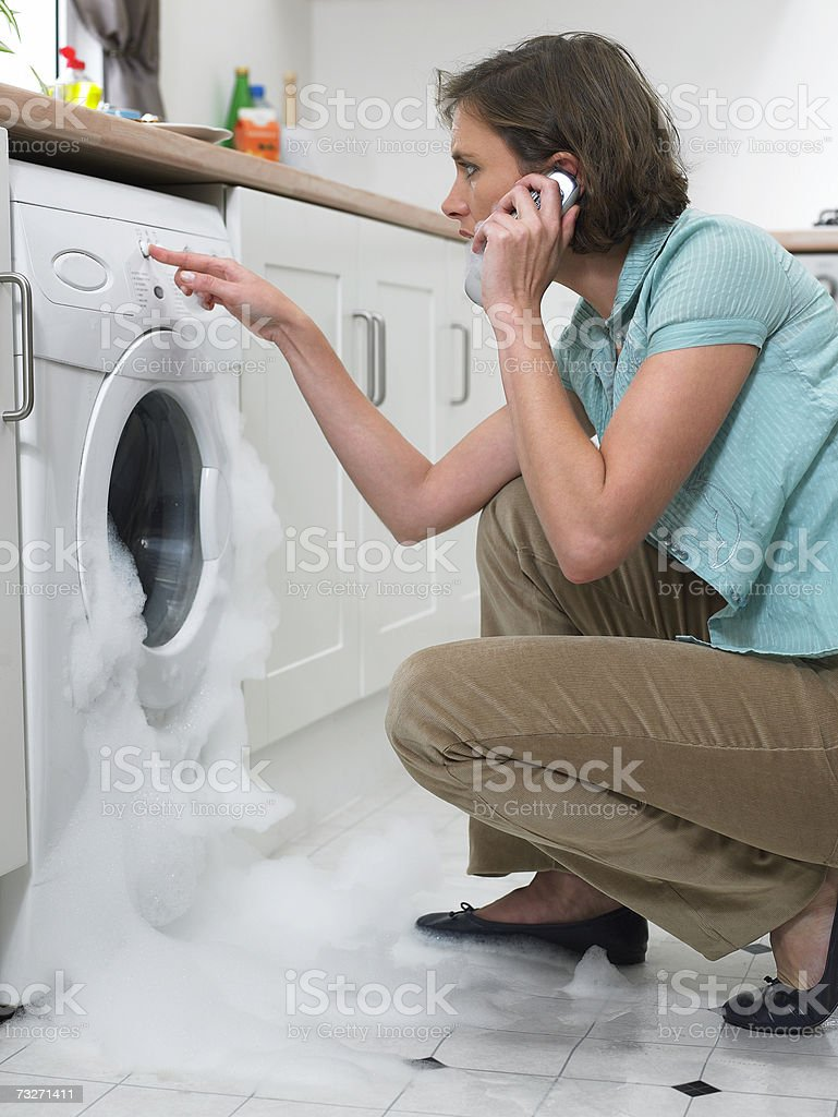 Woman using cell phone as washing machine overflows stock photo
