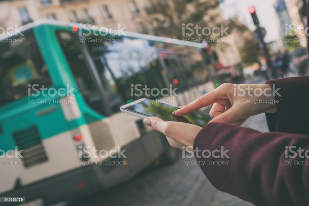 Woman using cellphone and crossing the street. stock photo
