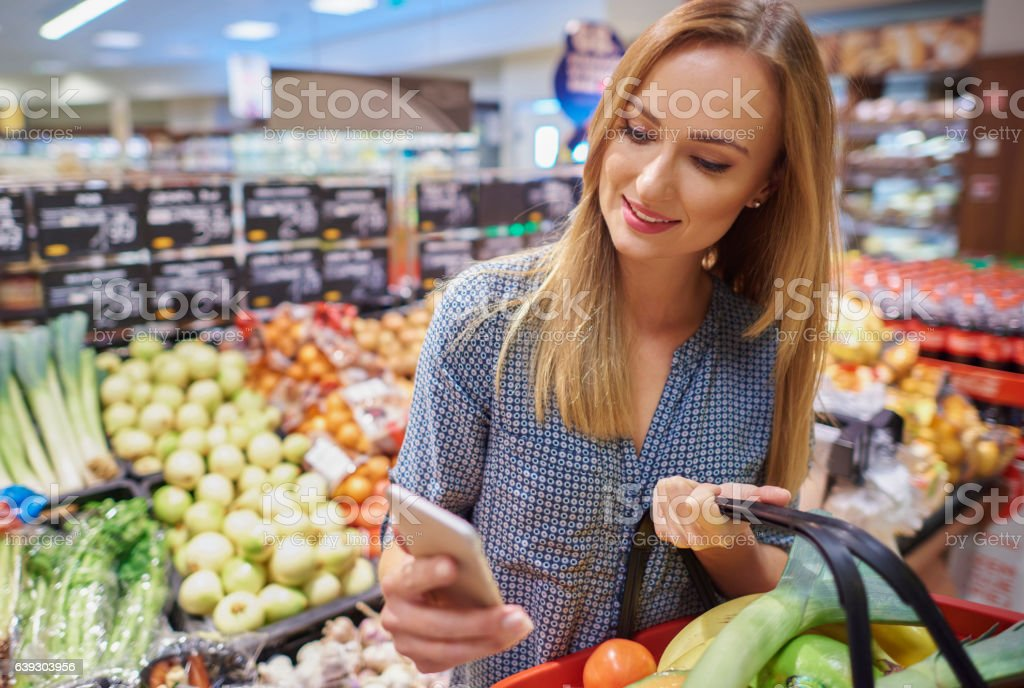 Woman using cellphone in grocery store stock photo