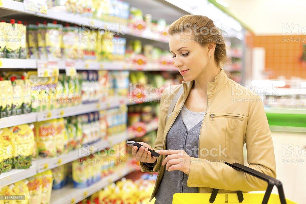Frau im Supermarkt mit cellphone – Foto
