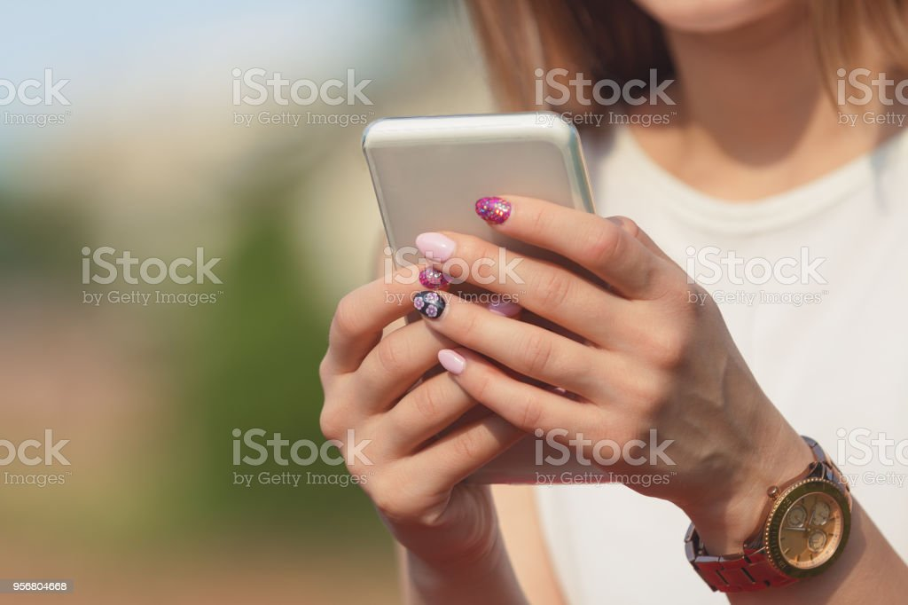 Woman using cellphone outdoors. stock photo