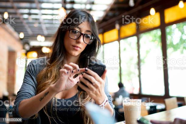 Woman using cellphone sitting in a cafeteria picture id1155000309?b=1&k=6&m=1155000309&s=612x612&h=bhp89z zheuwpakbmz 9ty jtqpukc4dw8mmifnvowg=