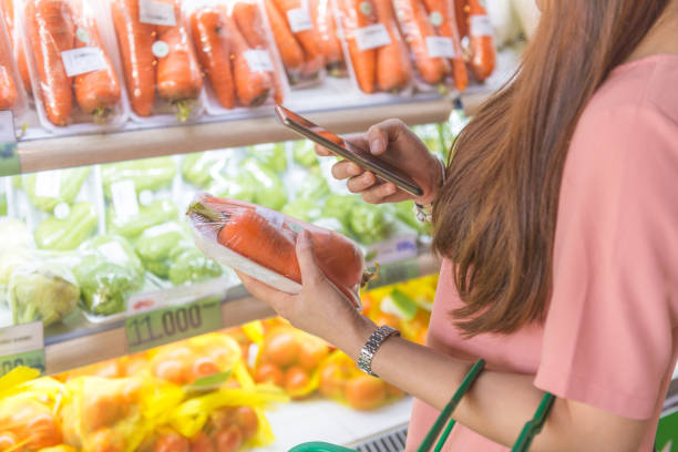 Woman using cellphone to scan code in grocery store stock photo