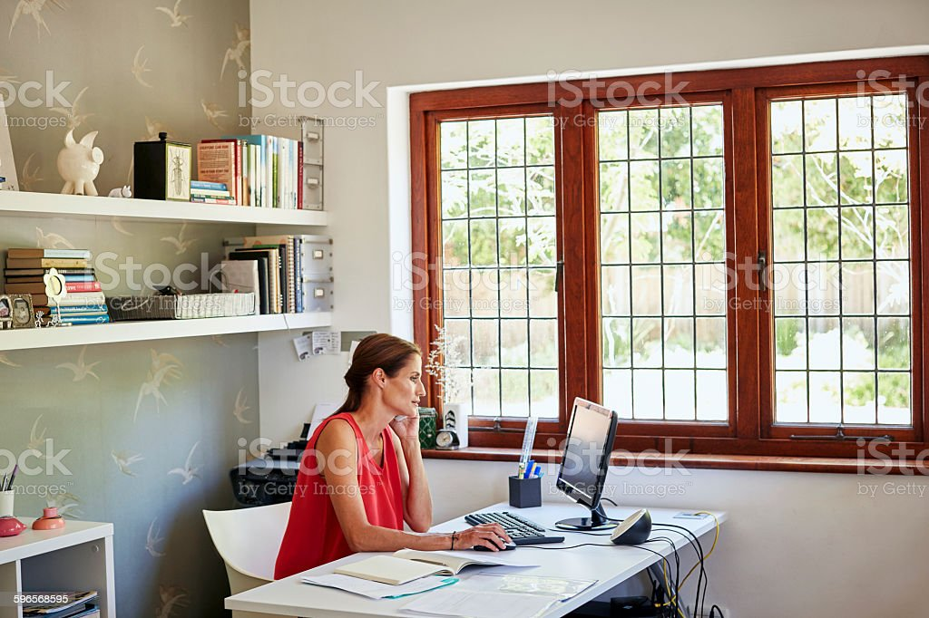 Woman using computer and mobile phone at desk stock photo