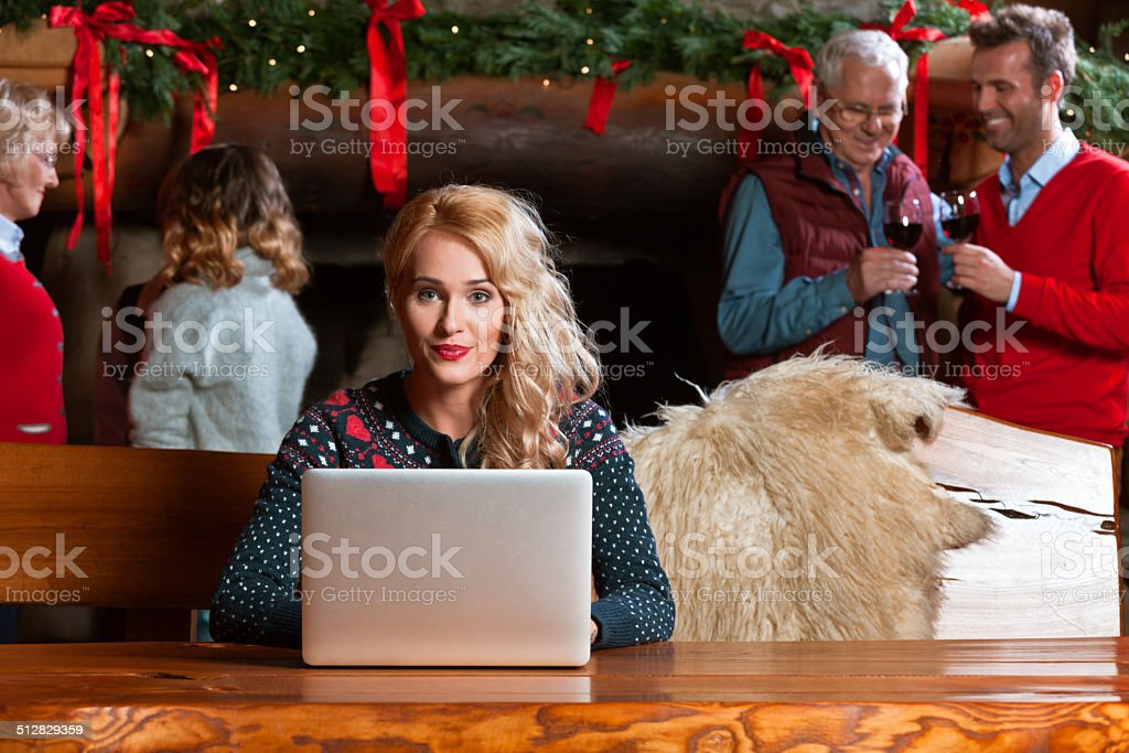 Woman using computer during Christmas A woman sitting by the table in the mountain house and using laptop with rest of family talking by the fireplace in the background. Active Seniors Stock Photo