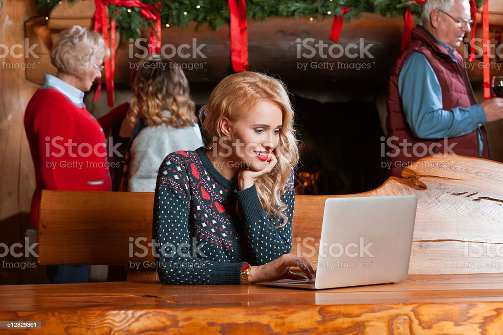 Woman using computer during Christmas A woman sitting by the table in the mountain house and using laptop with people talking by the fireplace in the background. Active Seniors Stock Photo